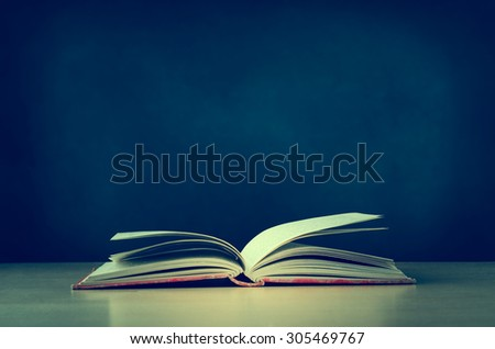 An old, worn, fabric covered red text book, lying opened on a school or college classroom desk.  Blackboard background provides copy space.  Crossprocessed for retro effect. - stock photo