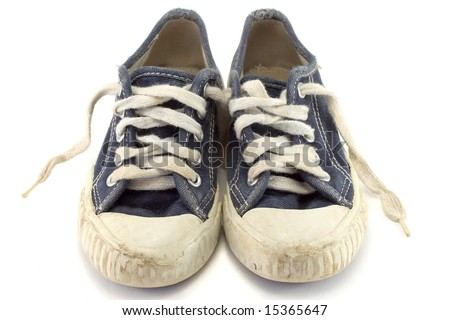 An old worn pair of children's jogging shoes. - stock photo