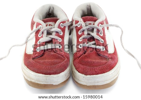 An old worn pair of children's sports shoes. - stock photo