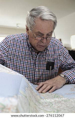 An older genteleman reading a map at home - stock photo