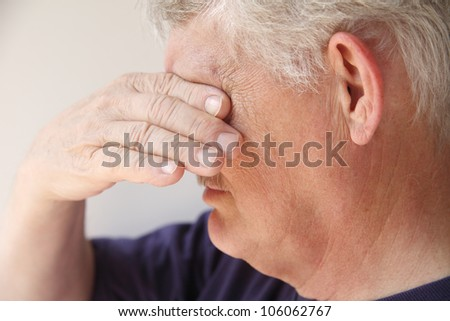 an older man covers his eyes as he is overcome with emotions - stock photo