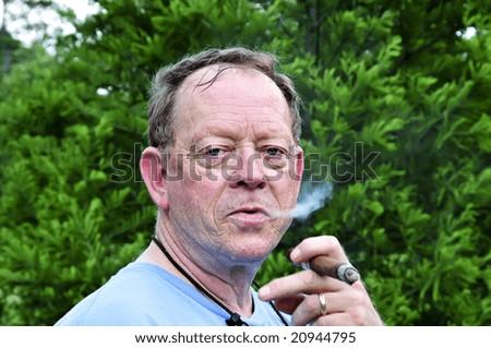 An older man enjoys a good puff on his cigar. - stock photo