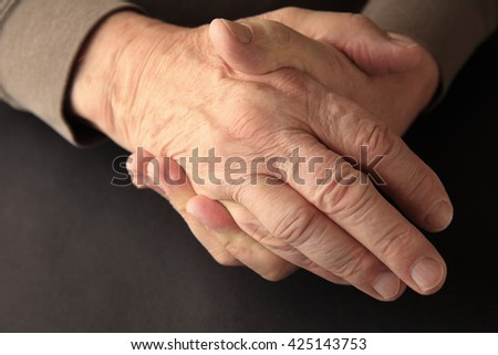 An older man grasps his hand on a black background with copy space. - stock photo