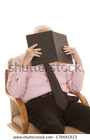 An older man sitting in his chair with a book up by his face studying. - stock photo