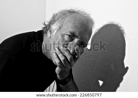 An older white man is looking directly at viewer with a concerned look in his eyes and covering his mouth. - stock photo