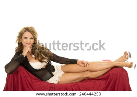 an older woman laying on her couch with her legs up. - stock photo