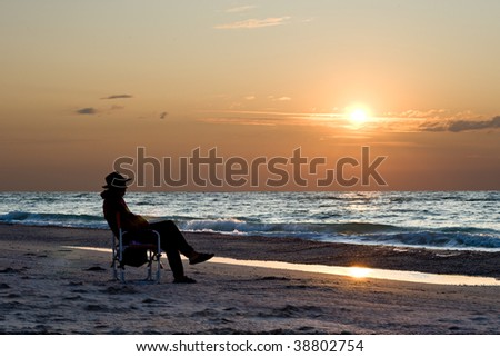 An oldman is watching the sunset at the sea - stock photo