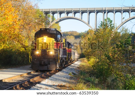 An oncoming passenger train under a high arch bridge in a scenic area - stock photo