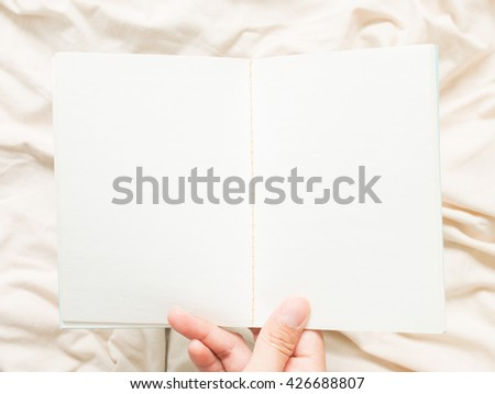 An open blank no lined  notebook on hand. - stock photo
