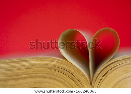 An open book with two pages shaped into a heart. - stock photo