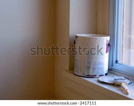An open can of paint is sitting on a window sill with the paint covered brush sitting beside it. The paint in the room is the same color of the paint in the can. Room is lit by the natural sunlight. - stock photo