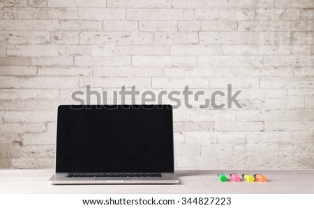 An open laptop on an office desk with flower, coffee, books in front of white brick wall background concept - stock photo