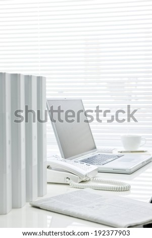 An open laptop, telephone, row of binders and a newspaper set on a desk. - stock photo