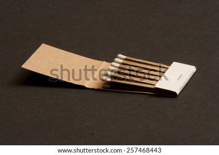 An open matchbook on a black background. - stock photo