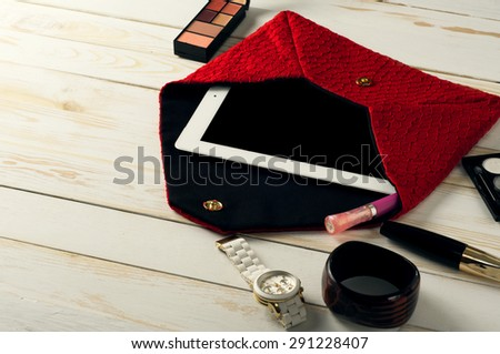 An open red  women bag with tablet computer in a white wooden table. Near the handbags are women's accessories. Mascara, eye shadow, watch, bracelet and lip gloss - stock photo