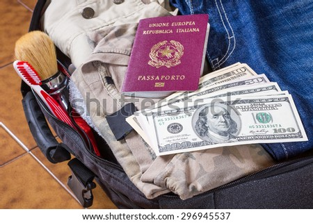 An open suitcase with clothes, personal effects, a buonch of dollars and an italian passport on it - stock photo