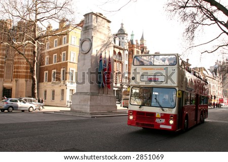 an open topped tour bus drives past the cenotaph in Whitehall in Central London, slight motion blur on the tour bus - stock photo