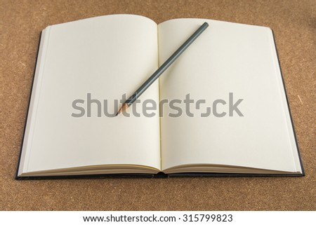 An Open Vintage Sketchbook or Notebook with pencil on Old Wooden Table. - stock photo