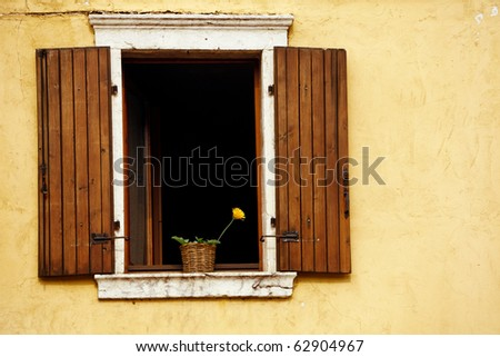 An open window with flower against a plastered textured wall and  wooden shutters.. - stock photo