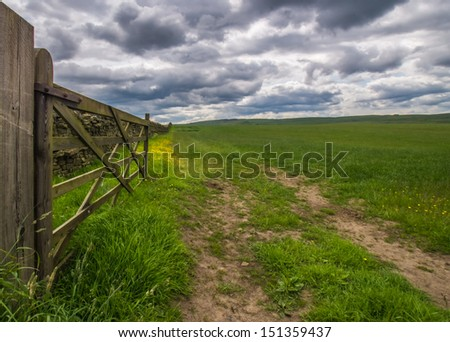 An open wooden gate on farmland in England - stock photo