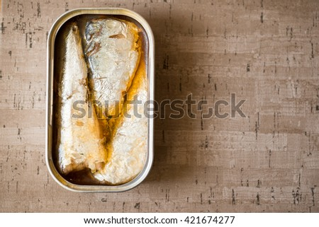 An opened can of sardines or herring in oil on wooden surface with copyspace. - stock photo