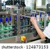 an operator monitors moving vodka bottles on conveyor - stock photo