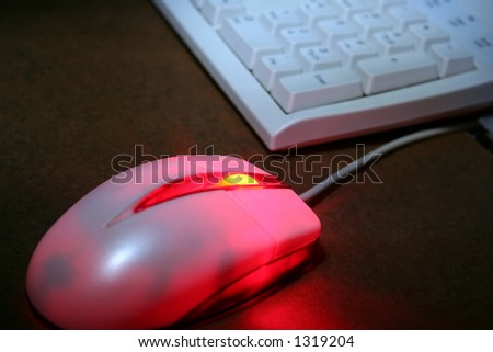 An optical mouse glowing red with keyboard in the background. - stock photo