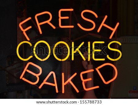 An orange and yellow neon sign reading Fresh Baked Cookies - stock photo