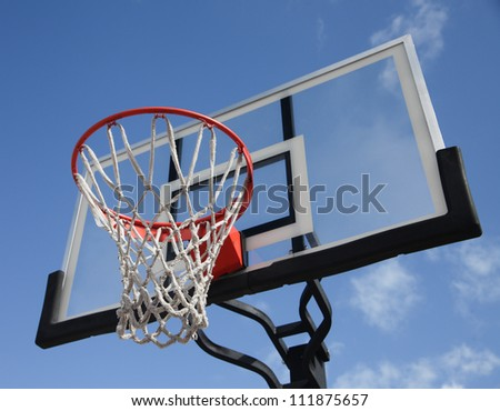 An orange basketball rim with white net and glass backboard against blue sky - stock photo