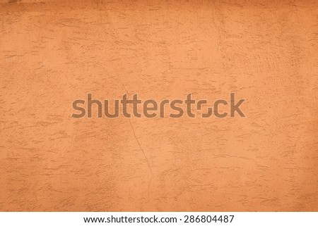 An orange, blank, slightly grungy stucco wall, perfect for background, messages, and texture. - stock photo