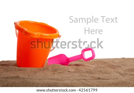 An orange bucket and pink shovel on a sandy beach with copy space on a white background - stock photo