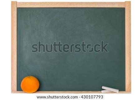 an orange in front of a blackboard - stock photo