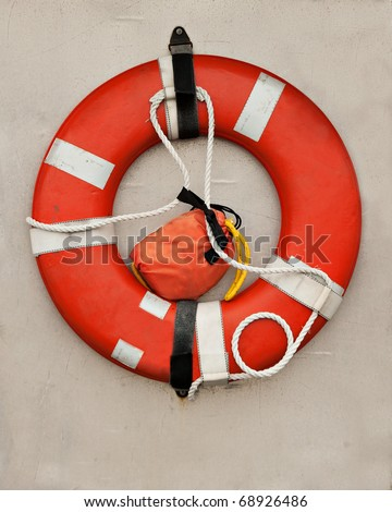 An orange life-preserver, or life-saver, ring hangs on the wall of a boat. - stock photo