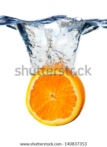 an orange slice, falling to the water, with the splashing - stock photo
