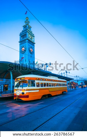 An orange street tram / train in downtown San Francisco at twilight. - stock photo
