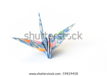 An origami bird with birds-pattern on a white background. Shallow depth of field, focus on the head. - stock photo