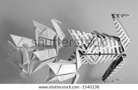 "An origami swan covered with the word ""mother"" leading a brood of five baby origami swans. - stock photo"