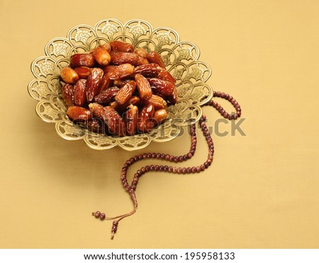 An ornamental bowl of dates and  prayer beads - stock photo