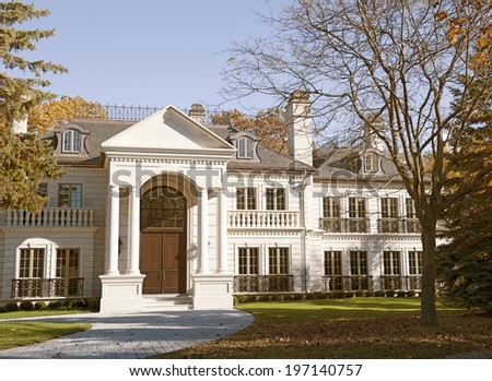 An ornate building with gigantic archway and doors, as well as many balconies. - stock photo