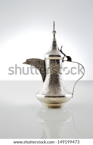 An ornate dallah which is a metal pot with a long spout designed specifically for making Arabic coffee - stock photo