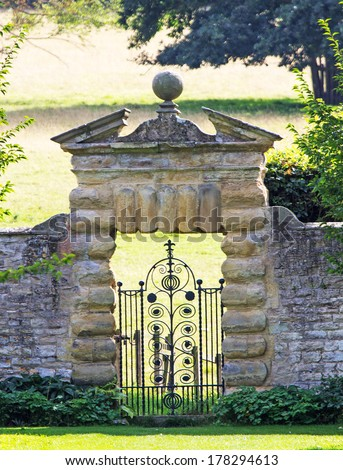An ornate ironwork gate set into a decorative wall leading from a sheltered garden into an extensive parkland - stock photo