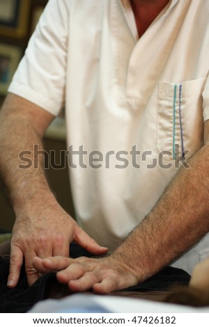 An osteopath is treating a patient - stock photo