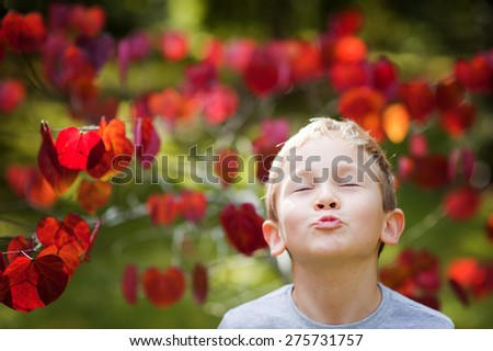 An outdoor portrait of a cute little boy blowing or sending a kiss into a camera with his eyes shut with a pretty tree with red heart shaped leaves in the background  - stock photo