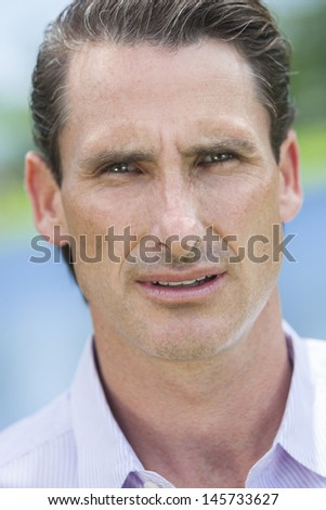 An outdoor portrait of handsome middle aged man shot with sunlight against a natural blue and green background - stock photo