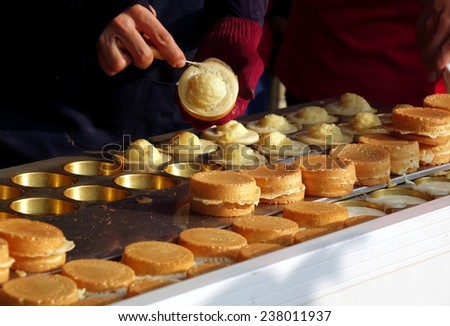 An outdoor vendor prepares sweet red bean cakes, a popular Chinese snack. - stock photo
