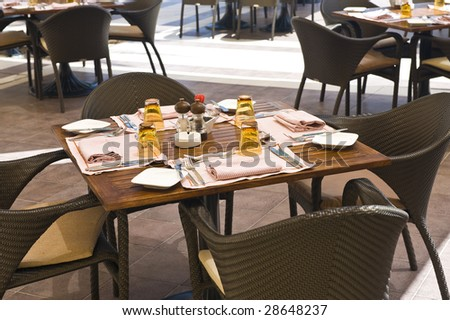 An outside restaurant at a hotel with nice place settings. - stock photo