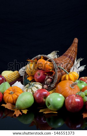 An overflowing cornucopia including pumpkins, grapes, gourds and leaves on a black background - stock photo