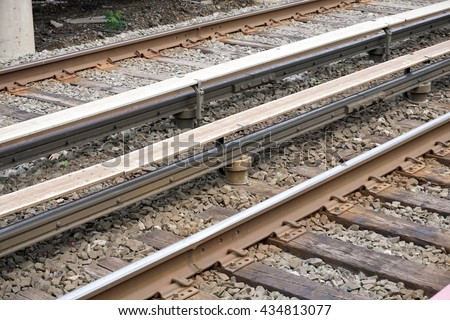 An overhead photo of the dangerous high voltage electrified third rail along railroad train tracks which powers the engine of commuter trains - stock photo