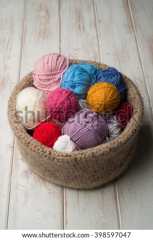 An overhead shot of balls of wool or yarn of different colours in a crocheted bowl. - stock photo