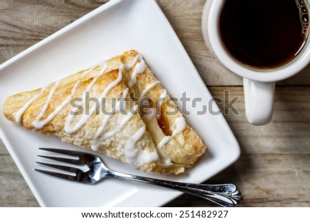 An overhead view of a frosted apple turnover and a cup of coffee - stock photo